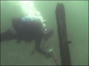In this October 2012 image from video provided by David J. Ruck, diver Tom Kucharsky passes timbers protruding from the bottom of Lake Michigan.