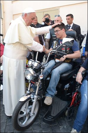 Pope Francis blesses a man in Harley-Davidson garb while spending time chatting with sick and disabled persons after the Mass in St. Peter's Square.