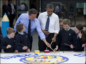 President Obama and British Prime Minister David Cameron help students paint a mural during a visit to the Enniskillen Integrated Primary School in Enniskillen, Northern Ireland, today.