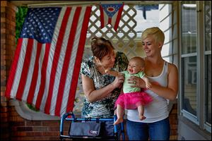 Sandra Vollmar, left, and Swanton resident Alexa Albring hold Ms. Albring's daughter, Aubri Berfield, 6 months, at Mrs. Vollmar's home in South Toledo. Ms. Vollmar was babysitting Aubri last month when she was struck by a hit-and-run driver. She managed to save the infant from injury.