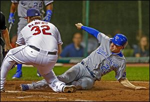 The Royals' Elliot Johnson, right,  slides home to score from third on a wild pitch by the Indians Matt Albers, left, who covered home plate on the play, in the ninth inning.