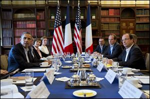 President Barack Obama meets with French President Francois Hollande during the G-8 summit, where discussions included globe-trotting corporate tax dodgers and Syria's's civil war.