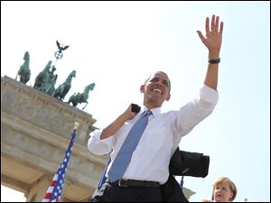 President Obama  waves to spectators before he  delivers a speech in front of the Brandenburg Gate  at Pariser Platz in Berlin, Germany, today.
