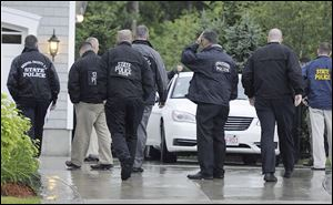 State and local police gather outside the home of New England Patriot's NFL football player Aaron Hernandez in North Attleborough, Mass., Tuesday.