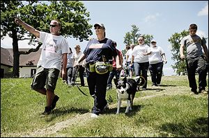 Tracy Finley of Toledo points as he walks with Ft. Wayne, Ind,. resident Gale St. John and her trained cadaver dog, Simon, at Navarre Park. The group searched the park Wednesday for Elaina Steinfurth.