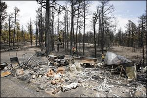Firefighters are pictured beyond a burned structure as they work hot spots on the Black Forest wildfire north of Colorado Springs, Colo., on Monday.