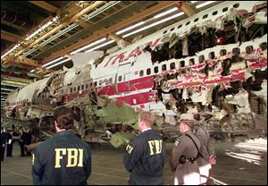 FBI agents and New York state police guard the reconstruction of TWA Flight 800 in Calverton, N.Y., in November, 1997. Flight 800 exploded and crashed July 17, 1996 while flying from New York to Paris, killing all 230 people aboard.