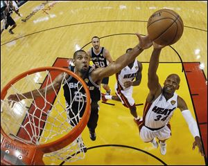 San Antonio Spurs center Boris Diaw (33) of France, blocks a shot to the basket by Miami Heat small forward LeBron James (6) during the first half of Game 6 of the NBA Finals basketball game.