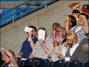 The Fryman family of Hamler shields their eyes from the evening sun during game.