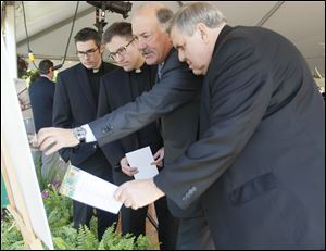 Kurt Darrow, chairman, president, and CEO of La-Z-Boy Inc., second from right, points out features of the site plan for the company's new headquarters to, from left, the Rev. Bryan Meldrum of Monroe, the Rev. Jim Smalarz, pastor of St. John Catholic Church, and the Rev. Terrence Kerner, pastor of St. Joseph and St. Martha churches. The building is on land acquired from the Sisters, Servants of the Immaculate Heart of Mary, a Catholic religious order that was founded in Monroe in 1845.