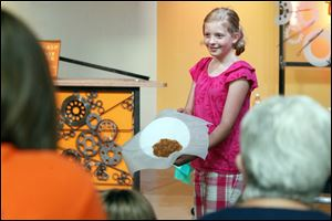 Darby Bryan, 10, of San Francisco, who is visiting her grandmother, shows 'fake, edible barf' that she made with Sylvia Branzei, author of 'Grossology,' at Imagination Station.