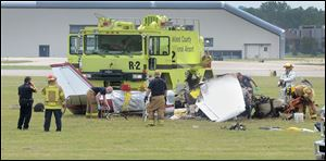 Emergency personnel looks over the scene of a plane crash at Oakland International Airport in Waterford, Mich.