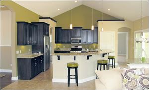 Dark maple cabinets are hung at varying heights for visual interest and topped by granite.