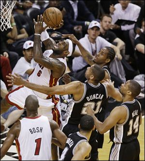 San Antonio Spurs' Kawhi Leonard tries to block a shot by Miami Heat's LeBron James (6) during the first half in Game 7.