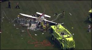 This frame grab from video provided by WDIV, WJBK, and WXYZ, shows emergency personnel examining a plane crash after a pilot and three passengers were killed shortly after takeoff.