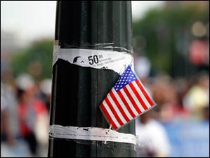 A US flag on a pole with an announcement of the United Auto Workers Detroit Freedom Walk.
