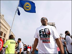 David Freeman from UAW Local 600 stands underneath a UAW flag at the start of the march on the corner of Woodward and Martin Luther King, Jr. Blvd.