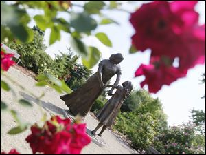 A sculpture of a mother and child stands in the Rose Garden in the Toledo Botanical Garden.