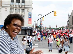 Marie Greer, from Detroit, reacts to seeing civil rights dignitaries and officials as the march floods past  the front of The Central United Methodist Church on the corner of Woodward Avenue and Adams.