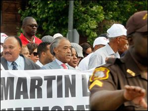 Martin Luther King'€™s son, Martin Luther King III, left, and the Rev. Al Sharpton, right, march down Woodward Avenue toward Hart Plaza.
