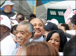 Martin Luther King's son, Martin Luther King III, center with mustache, looks out towrad the crowd.