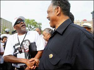 The Rev. Jesse Jackson, right, shakes hands with people on the march route.