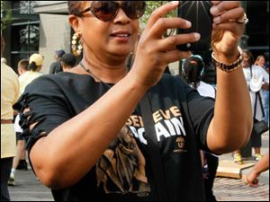 UAW member Yolanda Liggons, from Toledo, takes a picture of her granddaughter at the start of the march on the corner of Woodward and Martin Luther King, Jr. Blvd.