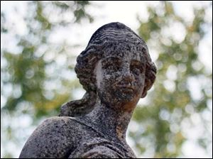 A sculpture of a young woman in the Toledo Botanical Garden.