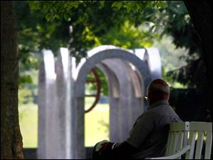 A man resting on a bench next to 'Small Park with Arches' by Alice Adams at Toledo Botanical Garden.
