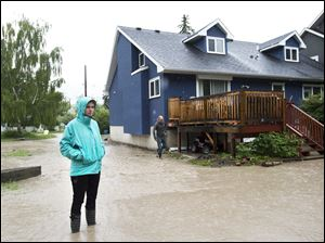A woman looks over the water damage from her back yard in the flooded community of Bowness.