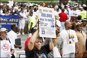 An original sign from the June 23, 1963, 'Walk to Freedom' is held high during Saturday's march in Detroit.