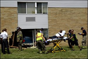 Members of the Toledo Fire Department help an injured man on a stretcher after the incident Friday.