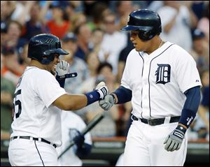 Detroit's Miguel Cabrera, right, is welcomed at home plate by teammate Brayan Pena after hitting a three-run home run.