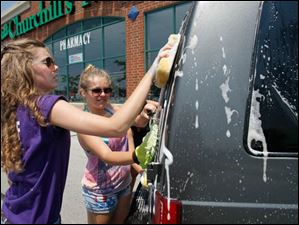 Amanda Martin, 16, left, and Victoria Gauthier, 16, wash the back of an SUV.