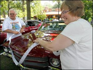 Larry Youngs, left, and his wife Karen Youngs measure a roll of 50/50 tickets around the length of a car for $10 for s customer who will have a chance to win money from the