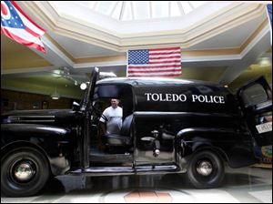 Mark Heilman of Toledo looks at the antique Toledo Police car in the middle of the Toledo Police Museum.