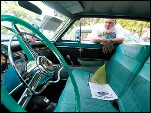 Owner Mick Kelly of Swanton looks into his 1954 Chrysler Newport New Yorker Deluxe that has the original steering wheel.