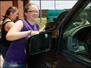 Val Kopp, 16, washes a windshield as Nautica Coutcher, 16, helps.