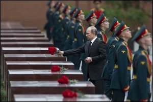 Russian President Vladimir Putin takes part in a wreath laying ceremony at the Tomb of the Unknown Soldier outside Moscow's Kremlin Wall in Moscow on Saturday to mark
