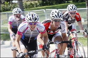 Sally Price, left, works to maintain her position against competitors Saturday during last year's Sylvania Cycling Classic near downtown Sylvania. On July 7, about 300 cyclists will participate. The contest starts with a men's race at 8 a.m. in Burnham Park, between Maplewood Avenue and Erie Street. More than 10 races will occur during the day. A c