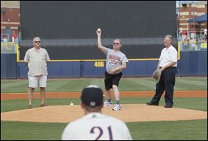 Sylvania police dispatcher Gary Siegel, who is ending his 35-year career, throws out the first pitch. Sylvania Police Chief William Rhodus, left, and Sylvania Mayor Craig Stough watch.