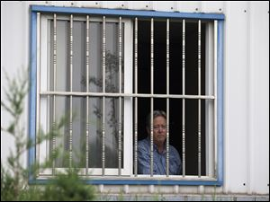 American Chip Starnes, co-owner of Specialty Medical Supplies, looks out from a window after he was held hostage by workers inside his plant at the Jinyurui Science and Technology Park in Qiao Zi township of Huairou District, on the outskirts of Beijing.