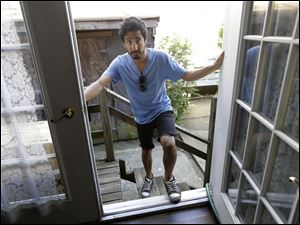 "Joseph Ferlito, 25, a resident of Lindenhurst, N.Y., poses at the back door of his Long Island home in Lindenhurst, N.Y.  Ferlito said his community banded together in the weeks after Superstorm Sandy and said FEMA was ""very unhelpful."""