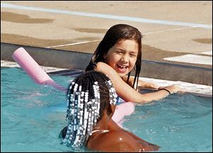 Jessica Bateman, 8, holds onto the side as she and friend Saniya Lincoln-Adams, 9, cool off Monday at Pickford Pool. Six of