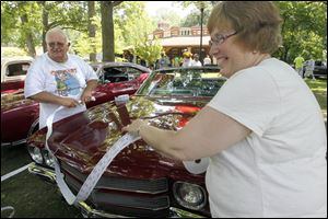 Larry Youngs and his wife, Karen Youngs, measure a roll of 50/50 raffle tickets around the length of a car for a customer. The raffle supports A Special Wish Foundation Inc.
