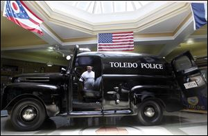 Mark Heilman of Toledo looks at the antique Toledo police car in the middle of the Toledo Police Museum. Sunday's car show also included old cruisers on loan from Cleveland.