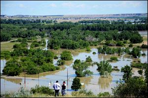 Residents look out from Scholten Hill as water floods an area of the River Flats in Medicine Hat, Albert on Sunday.