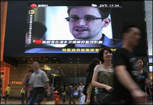 A TV screen shows a news report of Edward Snowden, a former CIA employee who leaked top-secret documents about sweeping U.S. surveillance programs, at a shopping mall in Hong Kong Sunday.