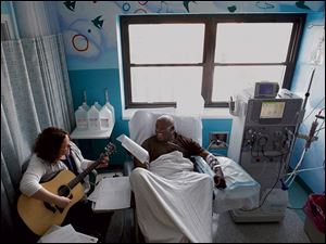 Sarah Tobias plays music for dialysis patient Chris Blackwell, 19, at Akron Children's Hospital.
