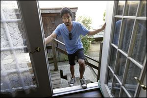 Joseph Ferlito, 25, a resident of Lindenhurst, N.Y., poses at the back door of his Long Island home in Lindenhurst, N.Y.  Ferlito said his community banded together in the weeks after Superstorm Sandy and said FEMA was